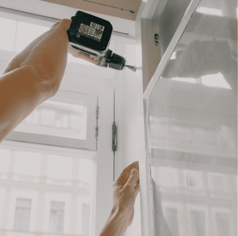man works on a window frame with an electric drill