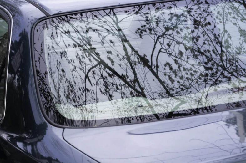 a black car with a reflection of trees in front